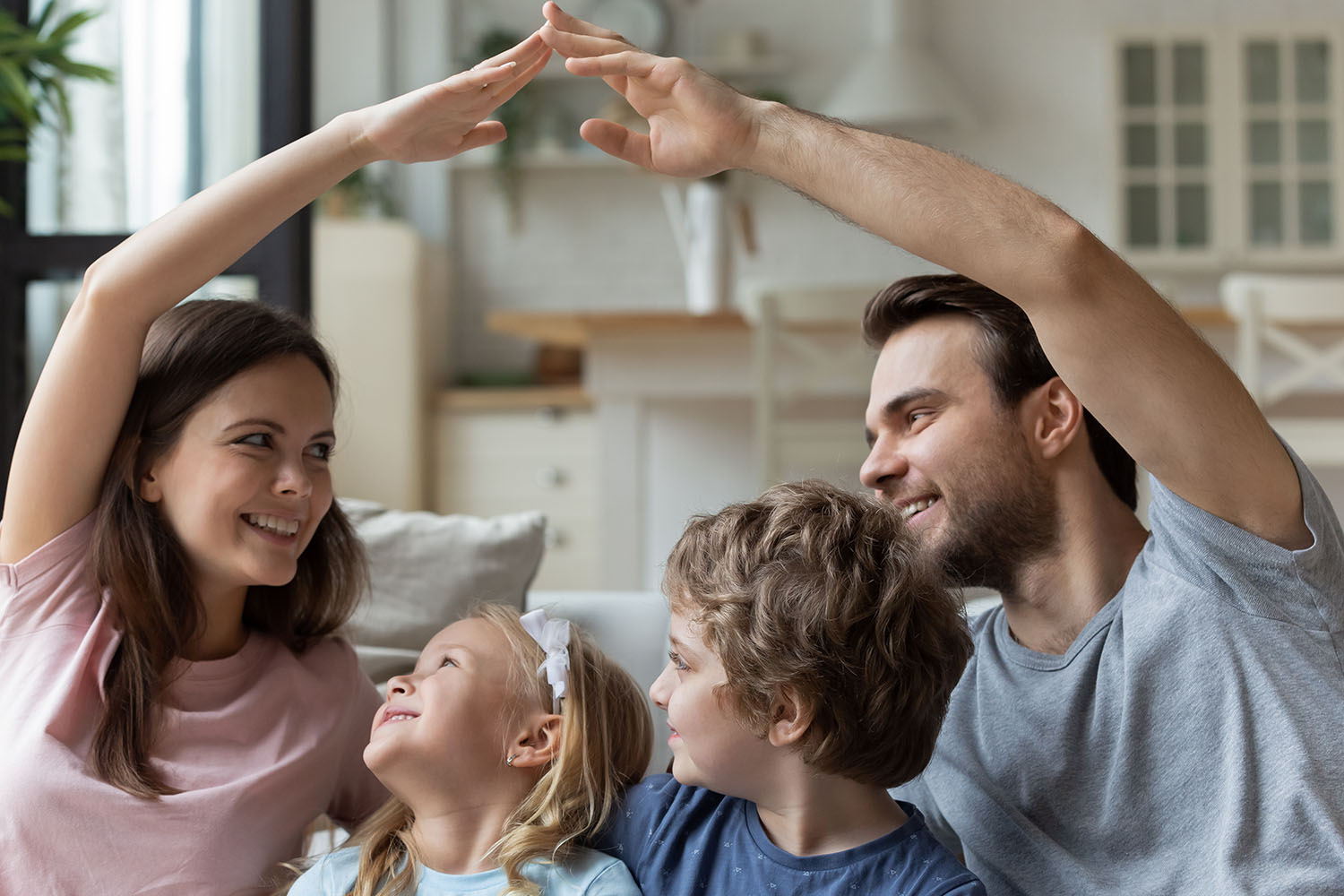 Smiling parents sitting with kids, making roof gesture with hands